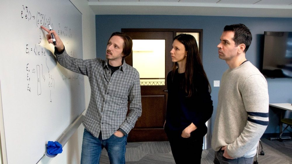 Left to right, Nick Mayhall, Sophia Economou, and Ed Barnes, all researchers and faculty members in the Virginia Tech College of Science, discuss quantum computing algorithms. Photo Virginia Tech.