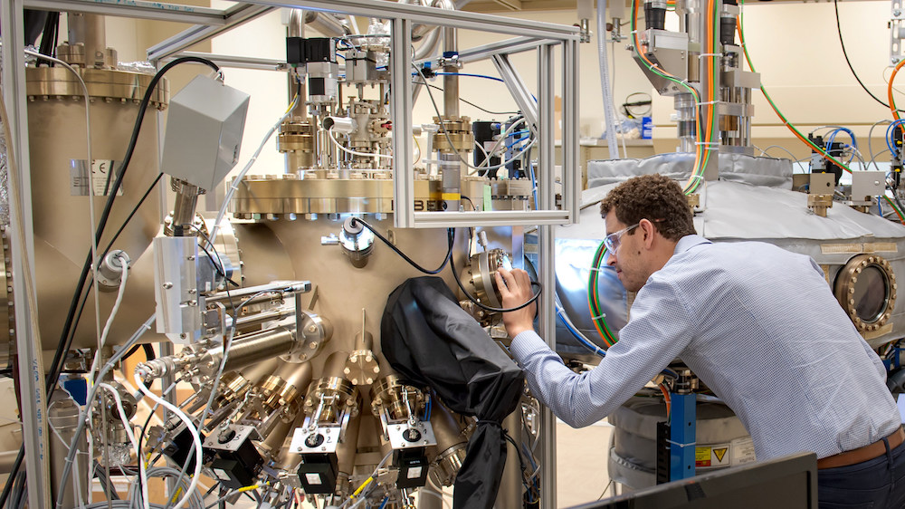 University of Chicago PhD graduate Sam Whiteley examines the sample chamber of Argonne's Riber molecular beam epitaxy tool, which grows materials that host quantum defects. Sam will join Chicago Quantum Exchange corporate partner HRL Laboratories in August 2019. Photo courtesy of Argonne National Laboratory.