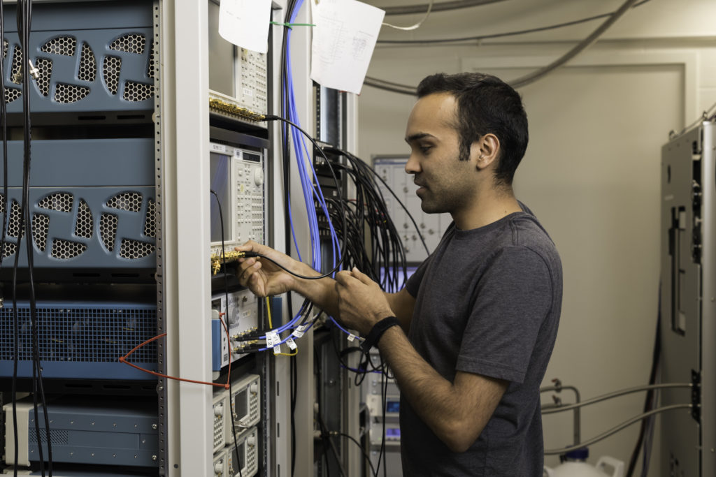 Yadav Kandel, a physics PhD student in assistant professor John Nichol's lab, uses an arbitrary waveform generator to manipulate qubits. (University of Rochester photo / J. Adam Fenster)