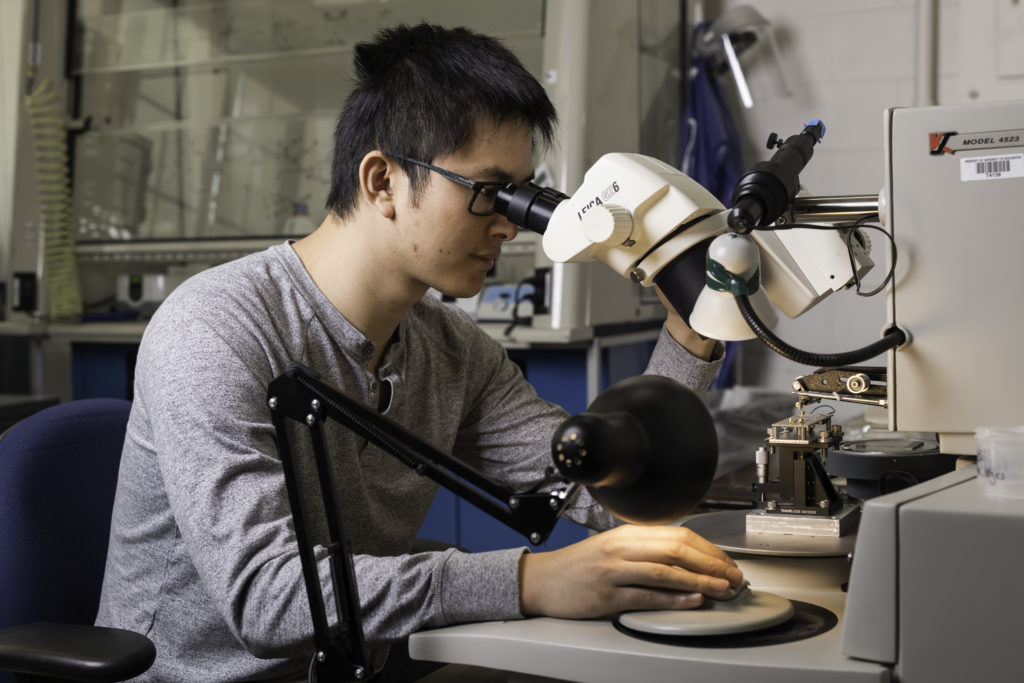 Doctoral student Haifeng Qiao uses a wire bonder to make electrical contact between the circuit board and the experimental device. (University of Rochester photo / J. Adam Fenster)