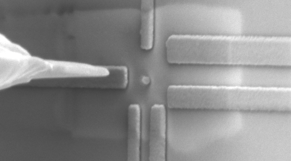 A single qubit component undergoing direct quantum measurements related to the materials' electronic characteristics, with the qubit component observed in the centre of the image (round particle of about 50 nanometres in size) and surrounded by rectangular nanoelectrodes prepared using facilities at the University.